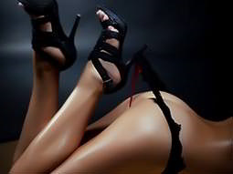 A woman's heel hooking a thong from a naked woman's bum