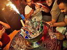 People sitting around a table with a sparkler coming out of a bucket of drinks