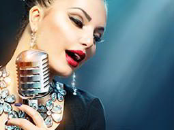 A close up of a woman singing into a silver mic