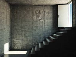 An empty, eerie room with a stone staircase to exit