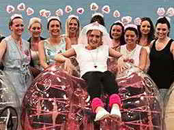 A group of nine hens wearing head boppers, surrounding one hen sitting on an inflated, pink zorb