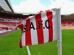 A red and white striped flag with 'S.A.F.C' on, against a background of the Stadium of Light
