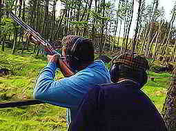 A man aiming a shotgun to the sky in a woodland clearing, with an instructor stood behind him