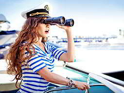 A woman in a striped blue and white top, looking through binoculars