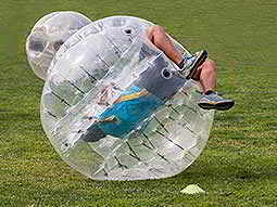 Two men doing flips in inflated zorbs