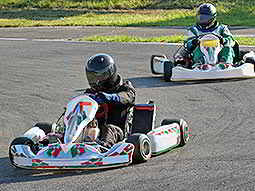 Two people driving white go karts on an outdoor track