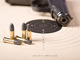 Five bullets on a paper shooting target, with a gun in the background