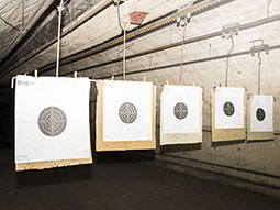 Five paper shooting targets hanging from the ceiling