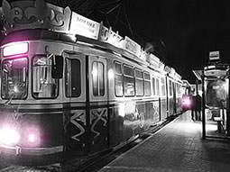 Black and white image of a tram at a station with bright lights on at the front