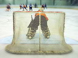 A goalie in net playing ice hockey