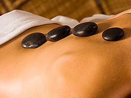 A man's back with four hot stones on