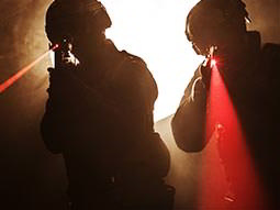Two men aim guns emitting visible red laser beams past the camera