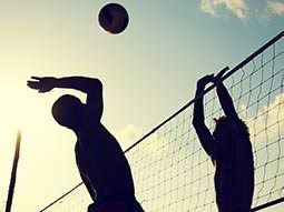 Two people playing volleyball, silhouetted against the sun