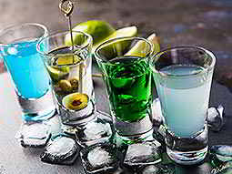 Four shot glasses filled with different variants of Absinthe