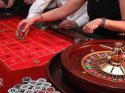 A man and a woman placing their bets on the roulette table