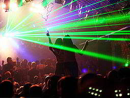 People dancing in a club to a backdrop of green strobe lights