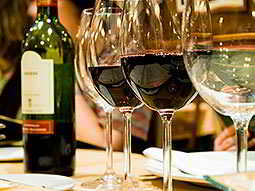 Two glasses of red wine in a line with two glasses of white wine, and a bottle in the background
