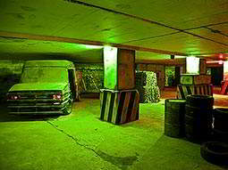 An indoor paintball arena, with tyres placed in the right corner and a 4x4 in the left corner