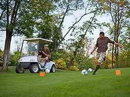 A man in golfing attire, kicking a football on a golf course with a man sat in a golf buggy behind him