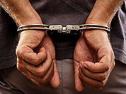 A man's hands handcuffed behind his back
