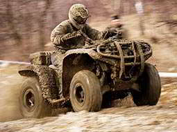 Close up of a person in overalls and mud, driving a muddy quad bike