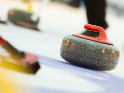 Curling stones and broom on a curling sheet