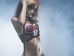 A woman holding onto a pole in pink and black underwear, to a smoky backdrop
