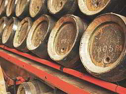 A stack of wooden barrels on a red shelf