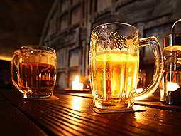 Two glasses of beer on a bar, with light shining through one