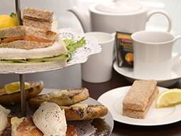 A cake stand with scones and sandwiches on next to a teapot and tea cups