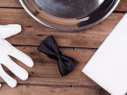A white glove and a bow tie lying out on a table