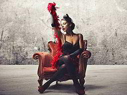 A woman sitting in a leather chair, posing with a red feather boa