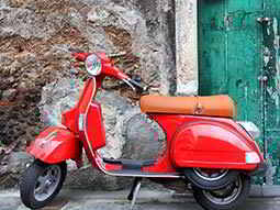 A red, parked up scooter in front of a wall