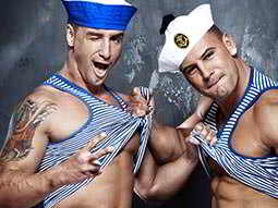Two men posing in sailor's outfits, lifting up each other's vests