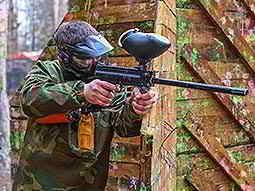 A man wearing a full-face paintball mask and camouflage overalls aims a paintball gun