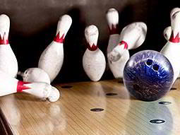 A bowling ball scattering 10-pin bowling pins