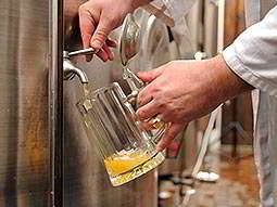A glass tankard being filled from a tap in a large metal vat