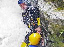 Close up of a man gorge scrambling and being splashed with water in a wetsuit and a helmet