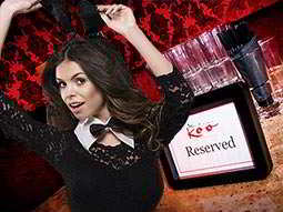 A booth table at Madade Koo with a 'reserved' sign on it and overlaid with a woman dancing in a bow-tie and bunny ears