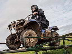 A blue quad bike being driven over a green metal obstacle