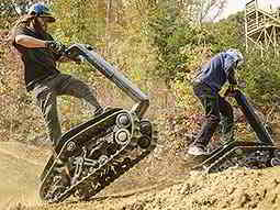 Two people driving a DTV Shredders over a muddy path