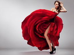 A woman holding up a red flamenco dress and showing her legs to a grey backdrop