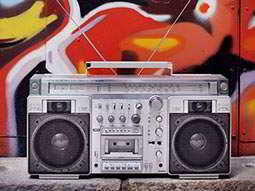 A boombox-style radio cassette player in front of a red, graffitid wall
