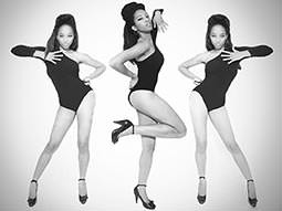 A black and white image of three women posing in leotards and heels