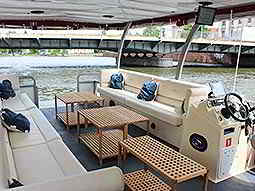 A seating area on an open-sided boat, on a river