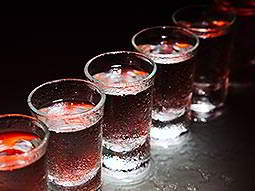 A row of filled shot glasses under red lights