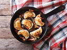 A pan filled with traditional Polish dumplings on a chequered tablecloth and wooden table