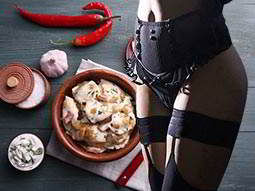 An image of a bowl of traditional Polish dumplings with other food nearby overlaid with the body of a woman wearing black lingerie