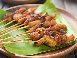 A row of small meat skewers