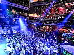 People dancing on a club dancefloor to a backdrop of blue strobe lights